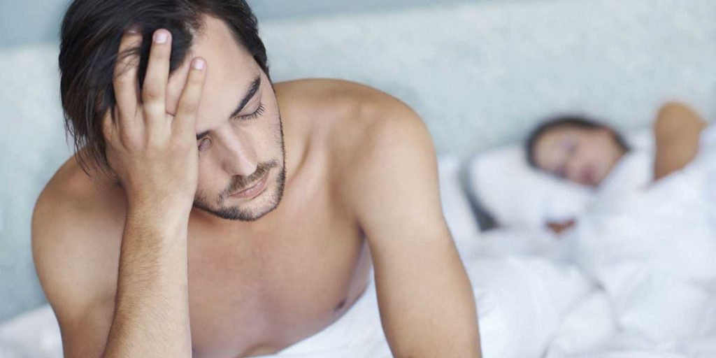 Man suffering from low libido side effect with woman in bedroom