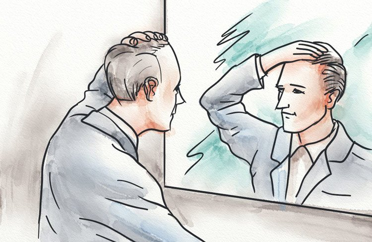 A young man looking at his hairline in the mirror