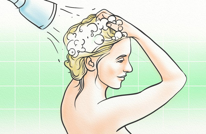 A woman washing her hair with Pura D'or Shampoo
