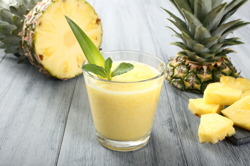 A glass of pineapple smoothie on a table