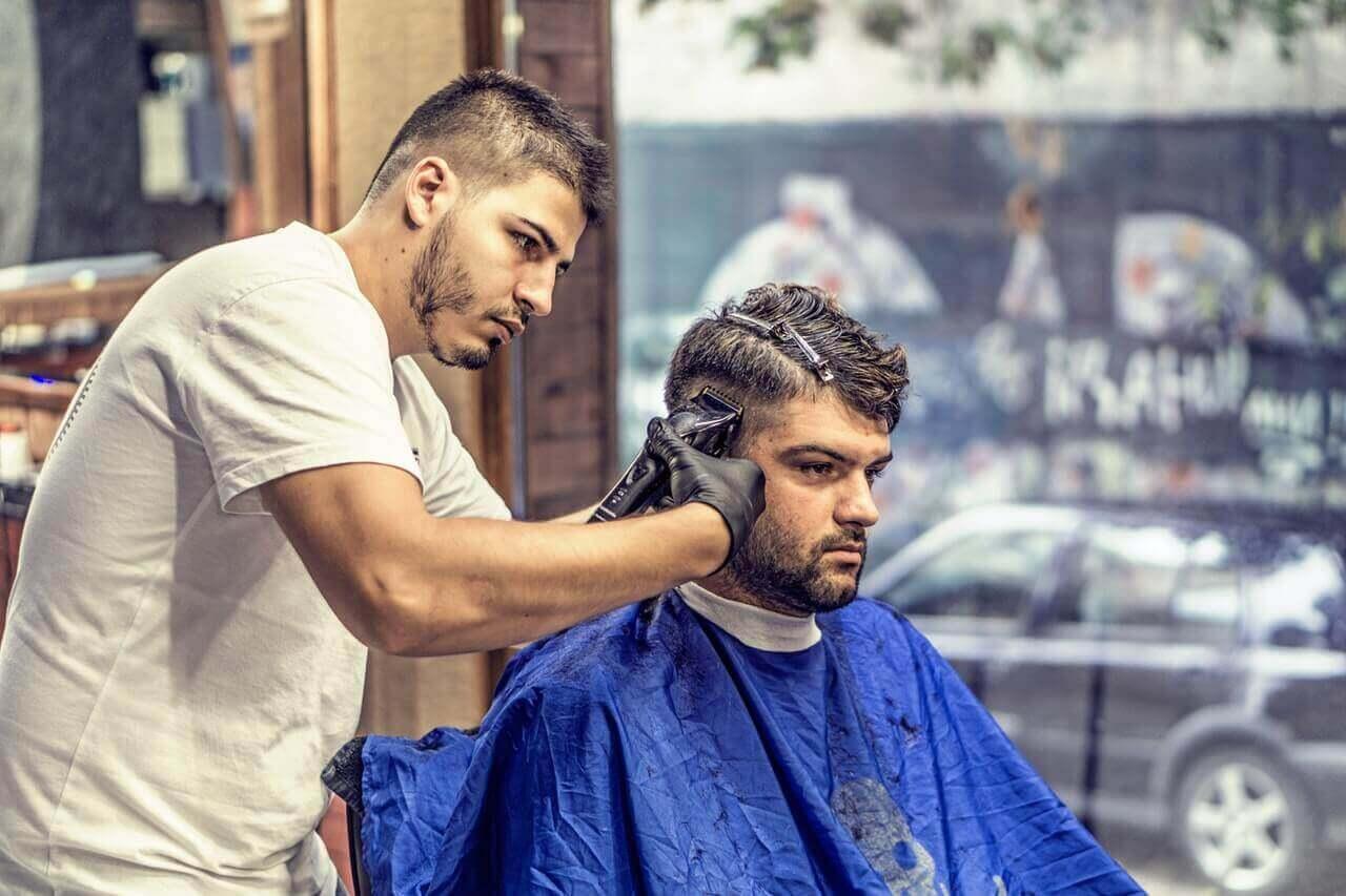 A man receiving a faded haircut