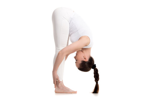 A woman performing the forward bend yoga pose